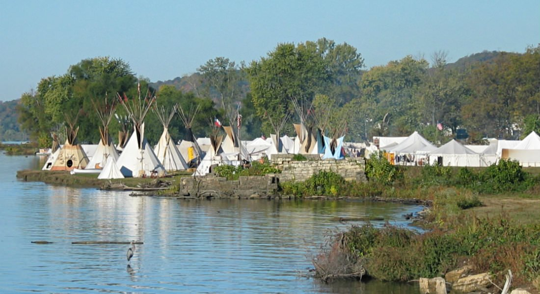 Tents and teepee tents on grass overlooking lake. Photo Credit Tom Foster