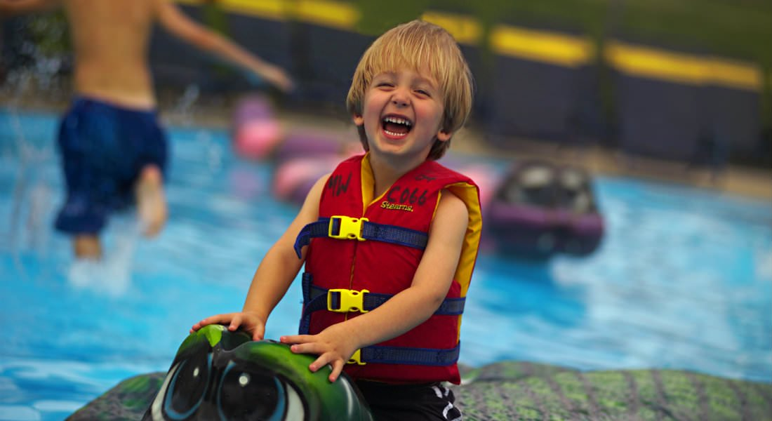Boy splashing in water and smiling boy on turtle sculpture at Magic Waters Water Park - Photo Credit Rockford CVB