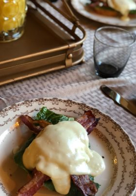 Round plate with gold trim with bacon, potatoes, juice decanter, grey tablecloth.