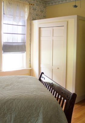 Corner view of floral wallpaper and yellow room, queen bed, view of sunroom through opened door, wood floor.