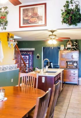 Slender kitchen with mustard, green and wallpaper border, wood dinining table, tiled floor, hanging plants, ceiling fan.
