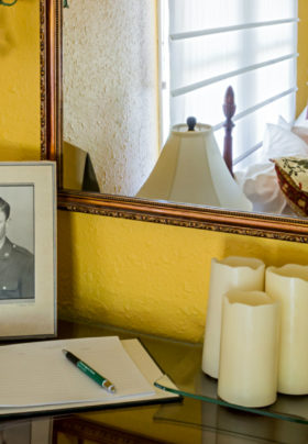 Mustard painted walls, guestbook on table with candles and brochures, mirror with reflection of bed and window.