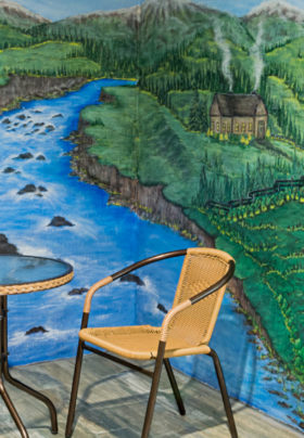 Canvas painting of flowing stream with table and chairs on wood deck, sitting room with rose and blue chairs.