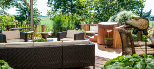 Covered wood deck with tan lawn furniture and hottub, view of farmland from deck.