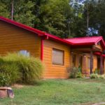 A photo of one of the tan cabins with a red roof.