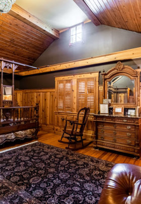 wide angle view of bedroom suite with antique king bed
