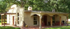 Adobe style house with covered porch, patio furniture, BBQ charcoal grill, picnic table, nestled in the trees