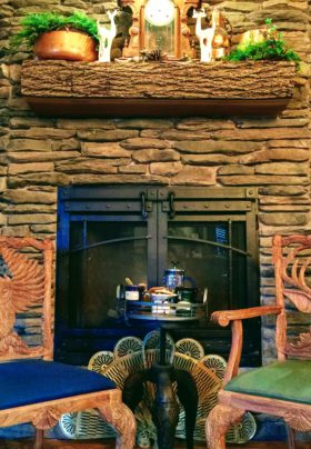 Two wooden chairs with blue and green cushions by stone fireplace and wood mantel, table with refreshments.