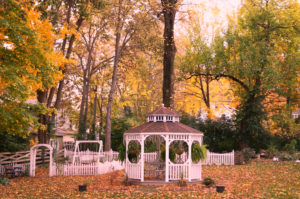 Leaf covered gazebo and lawn with colorful background at Blessings on State Bed & Breakfast, Jacksonville Illinois