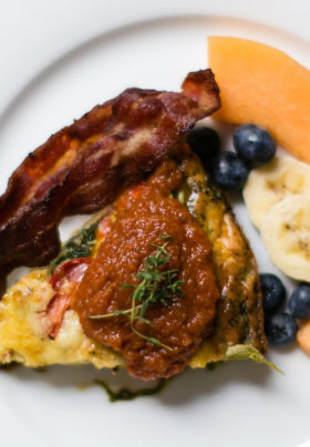 Photo of delicious breakfast vegetable frittata bacon and fresh fruit with a garnish of roasted pepper sauce