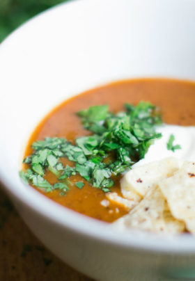 Photo of delicious bowl of black bean soup with queso fresco fresh cilantro and tortilla strips in white bowl