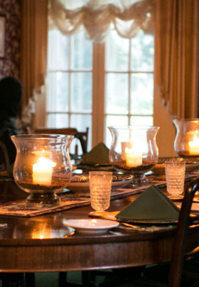 Formal dining room setting with Mahogany table candlelight and warm burgundy wallpaper