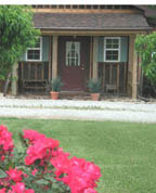 Teal and brown building with red door surrounded by greenery, clay pots with plants, red flowers planted in yard.
