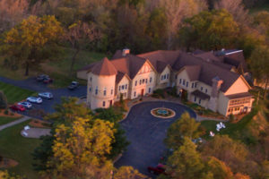 Aerial shot of peach colored building with brown roof surrounded by fall colored trees, circular driveway, parking lot with cars.