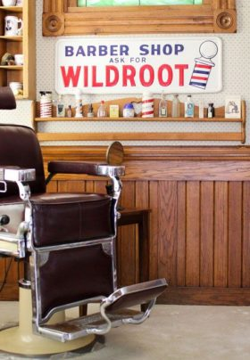 Old-fashioned barber chair, cream walls with wood accents, Sign with text Barber Shop Ask For Wildroot, shelves with mugs.