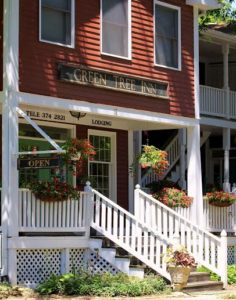 Red sided two-story building with sign Green Tree Inn, Stairs with white railing to porch, hanging potted flowers.
