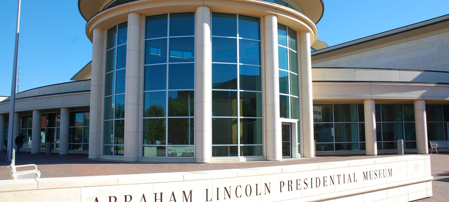 Circular building of Abraham Lincoln Museum, American flag on pole by bench.