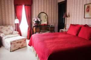 Pink striped wallpapered room with king bed with red comforter and shams, floral cover chair and ottoman, dresser with mirror.