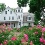 A white multi-story inn with turret, surrounded by pink rose bushes.