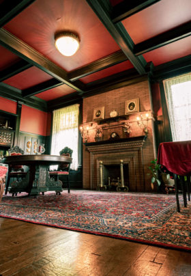 wide angle view of antique dining room with high red ceilings
