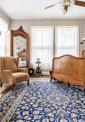 wide angle view of vibrant blue rug and antique queen bed with mirrored armoire