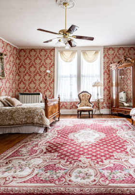 wide angle view of vibrant red and white room with antique bed and mirrored armoire