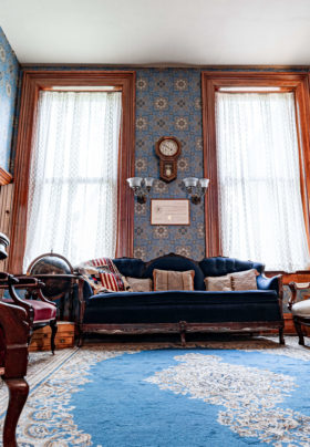 vibrant blue rug and antique couch in a room with an in wall antique safe