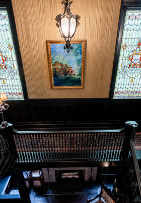 pair of iconic stained glass windows at the top of the stairs in the foyer