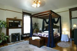 King hand-carved mahogany canopy bed in cream room, fireplace, stands with lights, cedar chest, sheered windows.