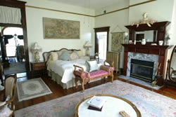 Luxury king bed guest room, fireplace and whirpool for two, wood floors with accent cream rug.