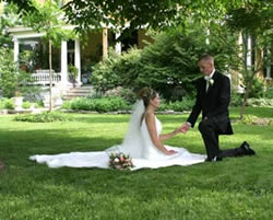 Bride and groom holding hands on front lawn with groom down on one knee at BEALL MANSION.