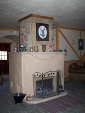 Fireplace in middle of room with black screen, cream mantel and shelf with knickknacks.