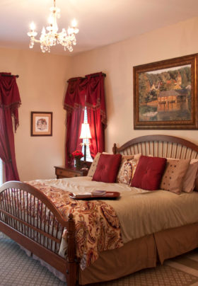 Peach bedroom with red curtains, queen bed with wooden head and footboards with floral peach comforter, framed painting.