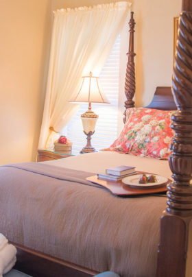 Sun shining through mini blinds on windows in peach room, luggage rack under window, queen bed with cherry frame.