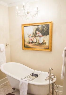 Tan bathroom with old-fashioned clawfoot tub, hand-held shower head, gold framed painting on wall, towel racks.