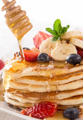 Stack of pancakes with sliced strawberries and bananas and blueberries, honey dipper stick drizzling honey.