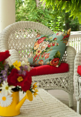 White red cushioned wicker furniture on porch with floral pillow, fresh flowers in yellow watering can on table.