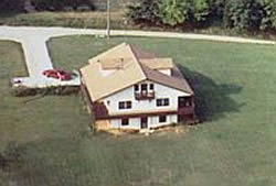 Aerial view of white three story house with tan roof, large yard, T shaped driveway with red car.