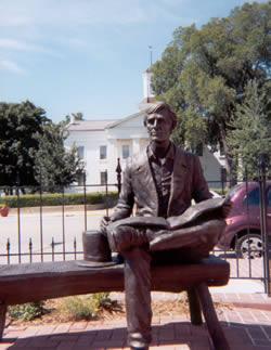 Metal statue of President Lincoln with top hat sitting on bench, iron fence, red car on street.