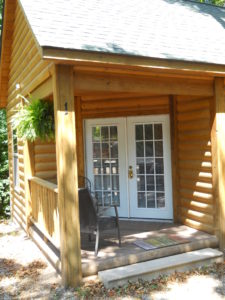 Log Cabin with double glass doors, two steps to get on porch with chairs,