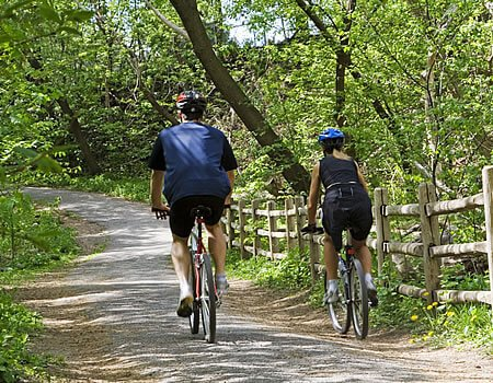 Two bikers wearing helmets and shorts riding along concrete trail through woods, wooden split rail fence on right.