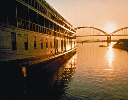 View of bridge over water at sunrise, building on water on left.