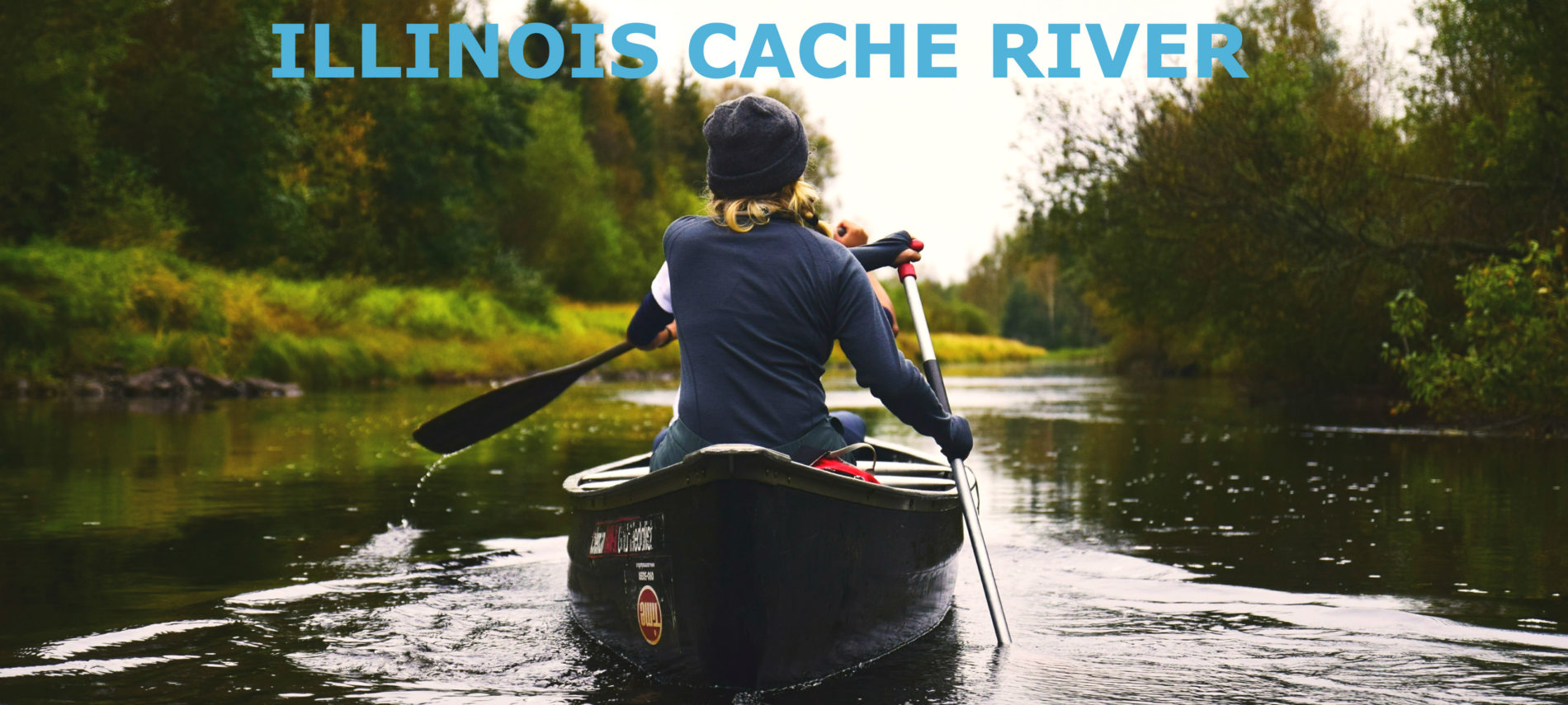 A photo of a woman canoeing down a tree-lined river.
