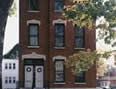 Slender multi-story red brick building with numerouse windows on each level, double glass door with wreaths.