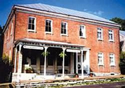 Two story red brick building with silver metal roof, covered porch with white pillars, hanging plants.