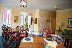 Mustard colored dining room with wood tables and chairs, ceiling fan and lights hanging, door to patio.
