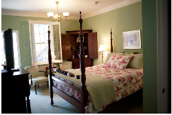 Green bedroom with queen bed covered with floral bedspread, corner wood hutch, tan carpet and chairs.