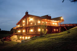 Well lit multi-level house at base of hill at dusk with wrap-around wood desk with railings.