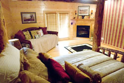Tan comforter on queen bed with oak head and footboards, striped wallpaper and cream wall with pictures, fireplace, red couch.