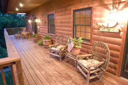 Cushioned wooden furniture sitting on covered porch of log cabin, potted plant with American Flag.
